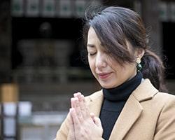 神社でお参りをする女性